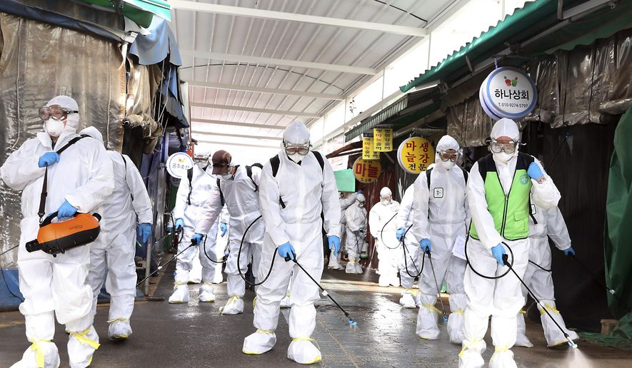 """Workers wearing protective suits spray disinfectant as a precaution against the coronavirus at a market in Bupyeong, South Korea, Monday, Feb. 24, 2020. South Korea reported another large jump in new virus cases Monday a day after the the president called for """"unprecedented, powerful"""" steps to combat the outbreak that is increasingly confounding attempts to stop the spread. (Lee Jong-chul/Newsis via AP)"""
