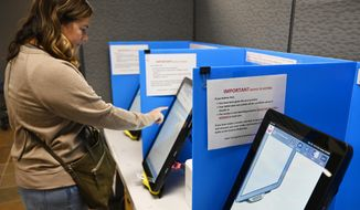 FILE-In this Tuesday, Nov. 5, 2019 file photoCourtney Parker votes on a new voting machine, in Dallas, Ga. Election integrity activists are raising concerns about Georgia's new voting machines, saying the large, bright, vertical touchscreens allow other people in the room to see a voter's selections in violation of ballot secrecy provisions in state law. In a petition filed Monday, Feb. 24, 2020, in Sumter County Superior Court against the five members of the county election board, the activists ask the court to order the board to have voters use hand-marked paper ballots rather than the touchscreen voting machines. (AP Photo/Mike Stewart, File)