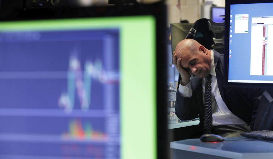 A specialist rests his head in his hand as he works on the floor of the New York Stock Exchange, Tuesday, Feb. 25, 2020. U.S. stocks fell in midday trading Tuesday, a day after the market's biggest drop in two years, as traders worry that the spreading coronavirus will threaten global economic growth. (AP Photo/Richard Drew)