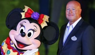 In this Sept. 11, 2015, file photo, Chairman of Walt Disney Parks and Resorts Bob Chapek poses with Minnie Mouse during a ceremony at the Hong Kong Disneyland, as they celebrate the Hong Kong Disneyland's 10th anniversary. The Walt Disney Co. has named Bob Chapek CEO, replacing Bob Iger, effective immediately, the company announced Tuesday, Feb. 25, 2020.  (AP Photo/Kin Cheung, File)