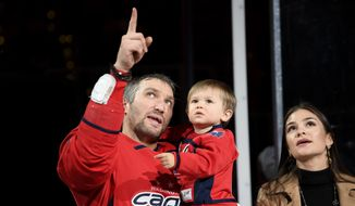 Washington Capitals left wing Alex Ovechkin, left, of Russia; Ovechkin's wife, Nastya, right; and son Sergei, center, watch the video screen on the scoreboard during a ceremony to honor Ovechkin for his 700th goal, before the team's NHL hockey game against the Winnipeg Jets, Tuesday, Feb. 25, 2020, in Washington. (AP Photo/Nick Wass)