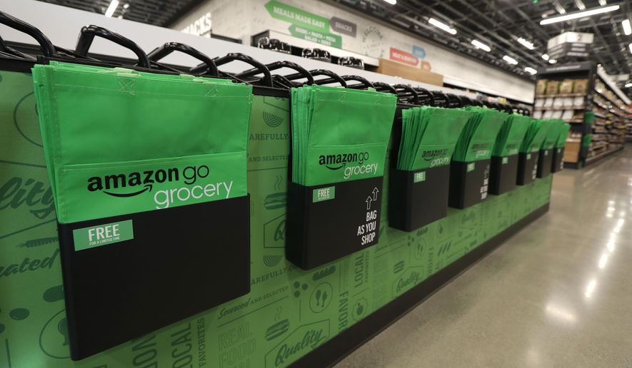 In this Feb. 21, 2020 photo, reusable shopping bags are displayed inside an Amazon Go Grocery store set to open soon in Seattle's Capitol Hill neighborhood. Following the opening of several smaller convenience-type stores using an app and cashier-less technology to tally shoppers' selections, the store will be the first Amazon Go full-sized cashier-less grocery store. (AP Photo/Ted S. Warren)