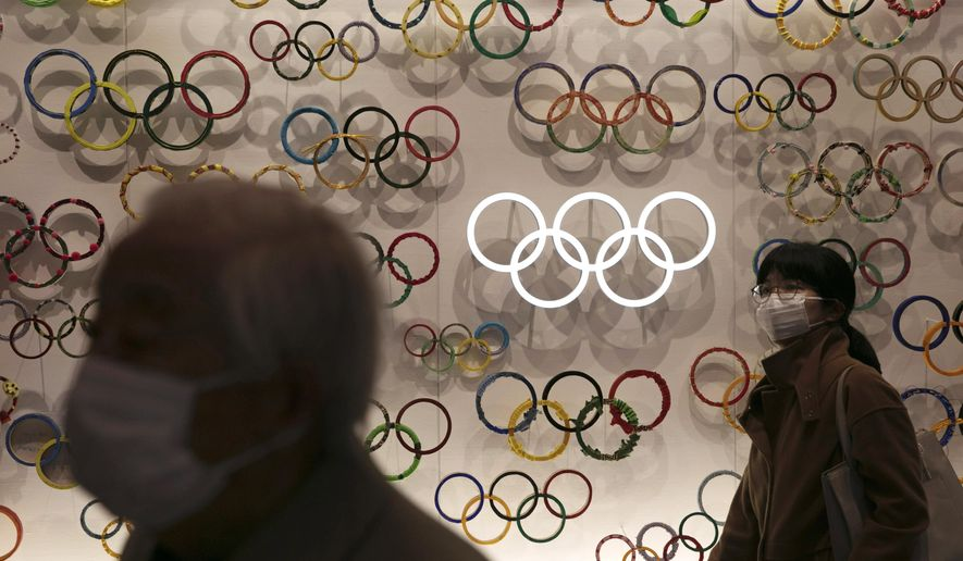 Two people wear masks as they visit the newly opened Japan Olympic Museum located near the New National Stadium, Sunday, Feb. 23, 2020, in Tokyo. (AP Photo/Jae C. Hong) ** FILE **