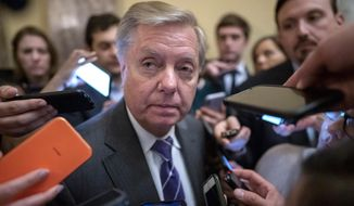 Senate Judiciary Committee Chairman Lindsey Graham, R-S.C., is surrounded by reporters after he and Republican lawmakers met with Attorney General William Barr about expiring provisions of the Foreign Intelligence Surveillance Act and other government intelligence laws, on Capitol Hill in Washington, Tuesday, Feb. 25, 2020. (AP Photo/J. Scott Applewhite)
