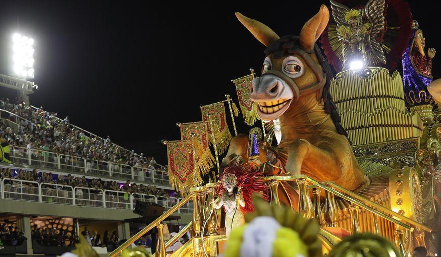 Performers from the Sao Clemente samba school parade on a float during Carnival celebrations at the Sambadrome in Rio de Janeiro, Brazil, Monday, Feb. 24, 2020. (AP Photo/Silvia Izquierdo)