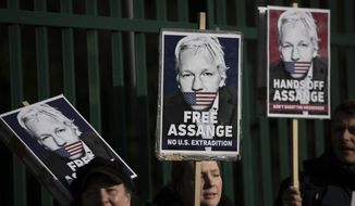 """Supporters of Julian Assange hold placards as they protest on the second day of a week of opening arguments for the extradition of Wikileaks founder Julian Assange outside Belmarsh Magistrates' Court in south east London, Tuesday, Feb. 25, 2020. U.S. authorities, want to try Assange on espionage charges. A lawyer for the Americans said the Australian computer expert was an """"ordinary"""" criminal whose publication of hundreds of thousands of secret military documents put many people at risk of torture and death. (AP Photo/Matt Dunham)"""