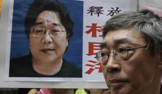 FILE - In this June 18, 2016, file photo, a picture of missing bookseller Gui Minhai is shown on a placard beside freed Hong Kong bookseller Lam Wing-kee, as the protesters are marching to the Chinese central government's liaison office in Hong Kong. A court in eastern China announced Tuesday, Feb. 25, 2020, that it has sentenced Gui, a naturalized Swedish citizen, to 10 years in prison. (AP Photo/Kin Cheung, File)