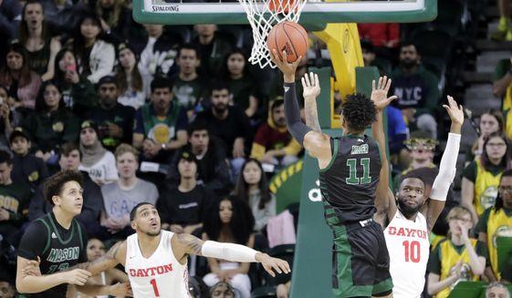 George Mason's Jordan Miller (11) shoots the ball as Dayton's Obi Toppin (1) and Jalen Crutcher (10) defend during the first half of an NCAA college basketball game, Tuesday, Feb. 25, 2020, in Fairfax, Va. (AP Photo/Luis M. Alvarez)