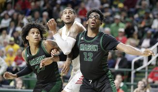 Dayton's Obi Toppin, center, positions for a free throw as George Mason's Javon Greene, left, and AJ Wilson defend during the second half of an NCAA college basketball game, Tuesday, Feb. 25, 2020, in Fairfax, Va. Dayton won 62-55. (AP Photo/Luis M. Alvarez)