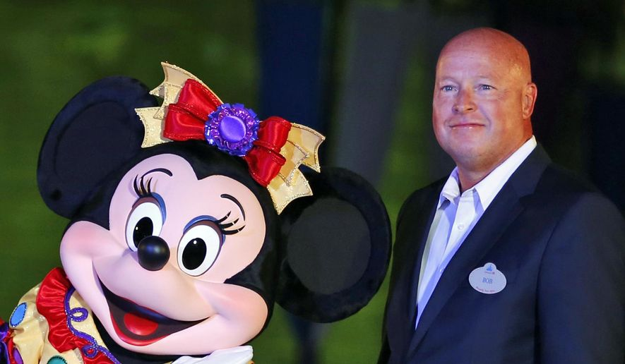 FILE - In this Sept. 11, 2015, file photo, Chairman of Walt Disney Parks and Resorts Bob Chapek poses with Minnie Mouse during a ceremony at the Hong Kong Disneyland, as they celebrate the Hong Kong Disneyland's 10th anniversary. The Walt Disney Co. has named Bob Chapek CEO, replacing Bob Iger, effective immediately, the company announced Tuesday, Feb. 25, 2020.  (AP Photo/Kin Cheung, File)