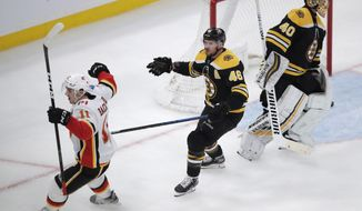 Calgary Flames center Mikael Backlund (11) celebrates after his goal against Boston Bruins goaltender Tuukka Rask (40) during the third period of an NHL hockey game in Boston, Tuesday, Feb. 25, 2020. Backlund scored twice in the Flames 5-2 win. At center is Boston Bruins center David Krejci (46). (AP Photo/Charles Krupa)