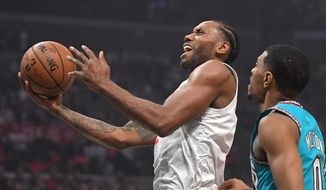 Los Angeles Clippers forward Kawhi Leonard, left, shoots as Memphis Grizzlies guard De'Anthony Melton defends during the first half of an NBA basketball game Monday, Feb. 24, 2020, in Los Angeles. (AP Photo/Mark J. Terrill)