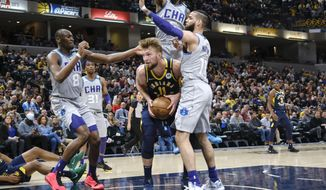 Indiana Pacers forward Domantas Sabonis (11) is surrounded by Charlotte Hornets defenders Bismack Biyombo (8), Jalen McDaniels (6) and Cody Martin (11) during the second half of an NBA basketball game in Indianapolis, Tuesday, Feb. 25, 2020. The Pacers won 119-80. (AP Photo/AJ Mast)