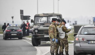 Italian Army soldiers and police check transit to and from the cordoned areas near Turano Lodigiano, Northern Italy, Tuesday, Feb. 25, 2020. Civil protection officials on Tuesday reported a large jump of cases in Italy, from 222 to 283. Seven people have died, all of them elderly people suffering other pathologies. (Claudio Furlan/Lapresse via AP)