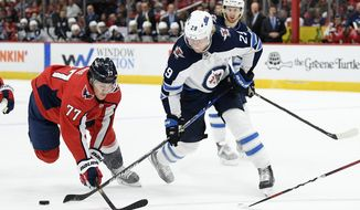 Winnipeg Jets right wing Patrik Laine (29) works for the puck next to Washington Capitals right wing T.J. Oshie (77) during the first period of an NHL hockey game Tuesday, Feb. 25, 2020, in Washington. (AP Photo/Nick Wass)