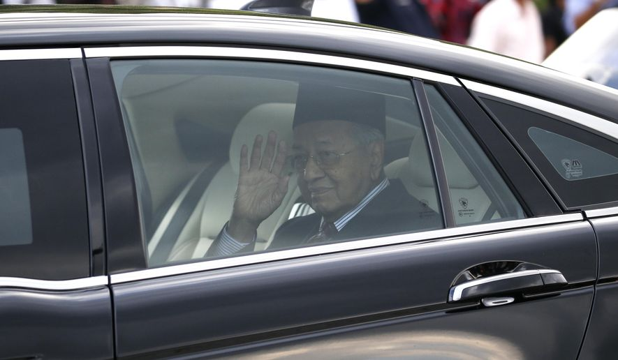 Malaysia's Prime Minister Mahathir Mohamad waves after granted an audience with the Malaysia's King Sultan Abdullah Sultan Ahmad Shah at the National Palace in Kuala Lumpur, on Monday, Feb. 24, 2020. Mahathir has resigned as the Malaysia's 7th Prime Minister on Feb. 24, 2020. (AP Photo/FL Wong)