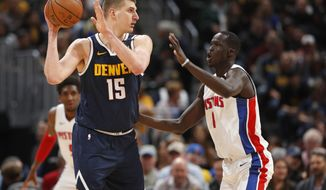 Denver Nuggets center Nikola Jokic, left, looks to pass the ball as Detroit Pistons forward Thon Maker defends in the first half of an NBA basketball game Tuesday, Feb. 25, 2020, in Denver. (AP Photo/David Zalubowski)