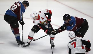 Ottawa Senators center Jean-Gabriel Pageau, center, fights for control of the puck with Colorado Avalanche center Nathan MacKinnon, left, and defenseman Cale Makar in the first period of an NHL hockey game Tuesday, Feb. 11, 2020, in Denver. (AP Photo/David Zalubowski)