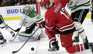 Dallas Stars' Anton Khudobin (35) defends the net against Carolina Hurricanes' Warren Foegele (13) during the third period of an NHL hockey game against the Carolina Hurricanes in Raleigh, N.C., on Tuesday, Feb. 25, 2020. (AP Photo/Chris Seward)