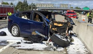 FILE - In this March 23, 2018, file photo provided by KTVU, emergency personnel work a the scene where a Tesla electric SUV crashed into a barrier on U.S. Highway 101 in Mountain View, Calif.  The National Transportation Safety Board says the driver of a Tesla SUV who died in a Silicon Valley crash two years ago was playing a video game on his smartphone at the time. Chairman Robert Sumwalt said at the start of a hearing Tuesday, Feb. 25, 2020 that partially automated driving systems like Tesla's Autopilot cannot drive themselves. Yet he says drivers continue to use them without paying attention. (KTVU-TV via AP, File)