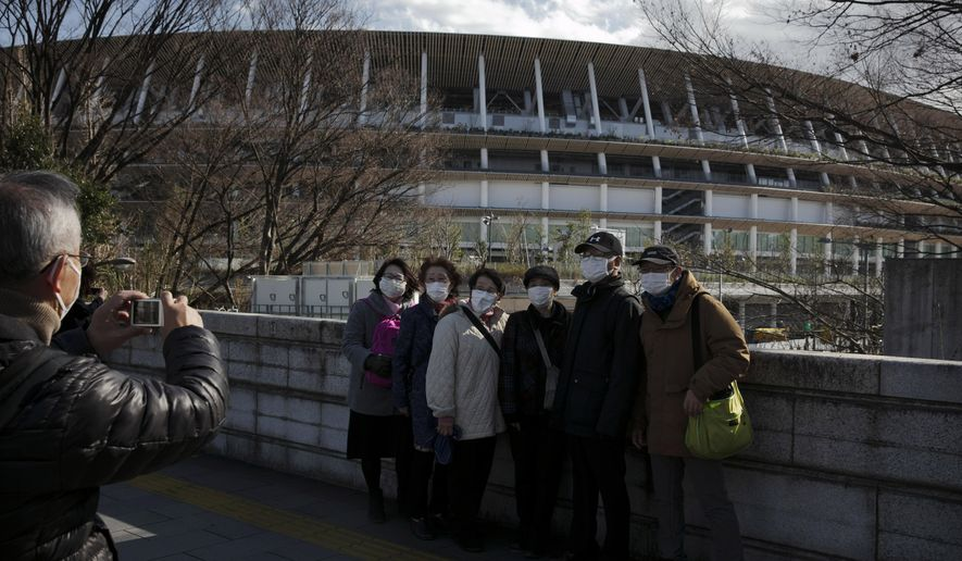 Tourists wear masks as they pause for photos with the New National Stadium, a venue for the opening and closing ceremonies at the Tokyo 2020 Olympics, Sunday, Feb. 23, 2020, in Tokyo. (AP Photo/Jae C. Hong) **FILE**
