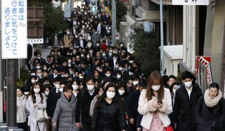 FILE - In this Feb. 20, 2020, file photo, people wear masks as they commute during the morning rush hour in Chuo district in Tokyo. China's massive travel restrictions, house-to-house checks, huge isolation wards and lockdowns of entire cities bought the world valuable time to prepare for the global spread of the new virus. (AP Photo/Kiichiro Sato, File)