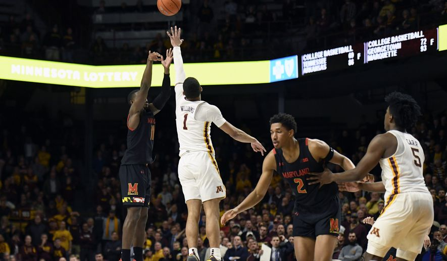 Maryland's Darryl Morsell (11) shoots the go-ahead 3-pointer over Minnesota's Tre' Williams (1) as Minnesota's Marcus Carr (5) defends against Maryland's Aaron Wiggins (2) during the second half of an NCAA college basketball game Wednesday, Feb. 26, 2020, in Minneapolis. Maryland won 74-73. (AP Photo/Hannah Foslien)