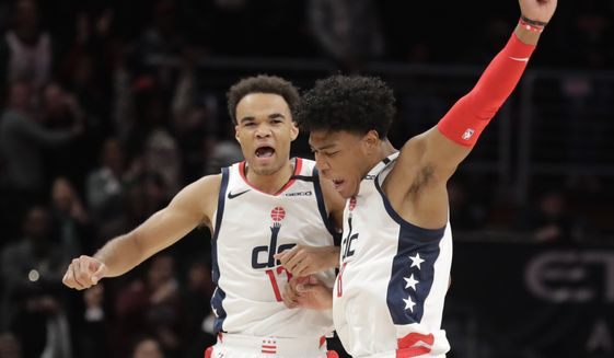 Washington Wizards' Jerome Robinson, left, celebrates with Rui Hachimura after making a 3-point shot during the fourth quarter of the team's NBA basketball game against the Brooklyn Nets, Wednesday, Feb. 26, 2020, in Washington. The Wizards won 110-106. (AP Photo/Luis M. Alvarez)