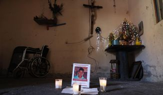 This Feb. 13, 2020 photo shows a memorial for Juan Carlos Medina Serrano in his family's living room, the day his remains were buried, in Irapuato, Guanajuato state, Mexico. Armed men took the 32-year-old from his house on Dec. 3. A few days later, authorities found 19 rotting bodies buried in a backyard in a nearby town, but it took two months for them to notify his wife that her husband was one of the bodies. (AP Photo/Rebecca Blackwell)