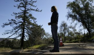 In this Tuesday, Feb. 25, 2020, photo, Jason Meek, whose Northern California wine country home was destroyed in 2017, stands in the driveway and looks out at the remains of his home in Santa Rosa, Calif. A $13.5 billion settlement between victims, including Meek, of California's catastrophic wildfires and Pacific Gas & Electric was supposed to bring some peace and hope to people still reeling from the devastation. Instead, it has sparked confusion, resentment, suspicion and despair as the victims, government agencies, and lawyers grapple for their piece of the settlement fund. (AP Photo/Eric Risberg)