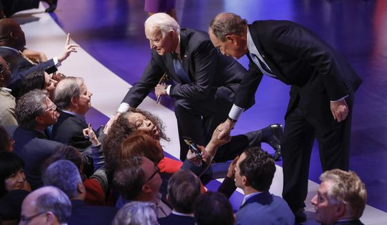 Democratic presidential candidates, former New York City Mayor Mike Bloomberg, right, and former Vice President Joe Biden, left, greet supporters at the end of the Democratic presidential primary debate at the Gaillard Center, Tuesday, Feb. 25, 2020, in Charleston, S.C., co-hosted by CBS News and the Congressional Black Caucus Institute. (AP Photo/Patrick Semansky)