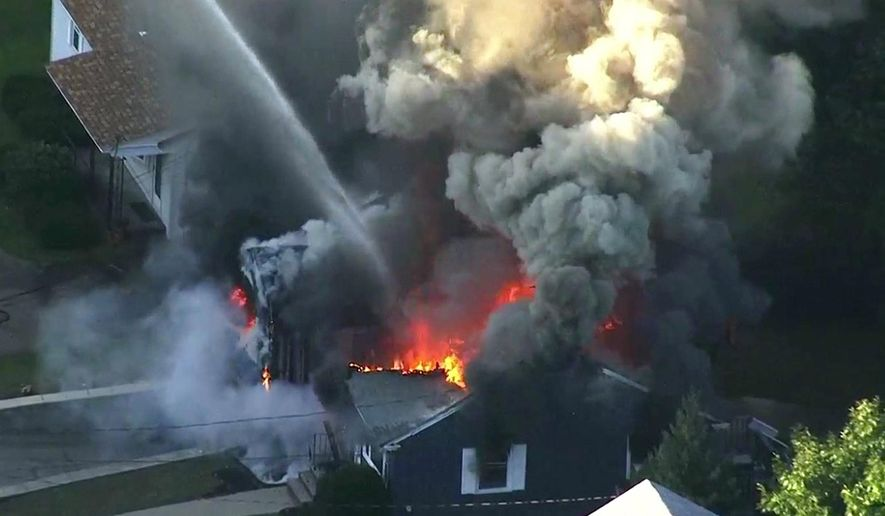 FILE - In this Sept. 13, 2018 file image from video provided by WCVB in Boston, flames consume the roof of a home following an explosion in Lawrence, Mass. The U.S. Attorney's office in Boston announced Wednesday, Feb. 26, 2020, that Columbia Gas Columbia agreed to plead guilty to violating the Pipeline Safety Act following an investigation into the catastrophic gas explosions. (WCVB via AP, File)
