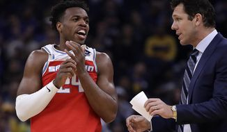 Sacramento Kings' Buddy Hield, left, speaks with coach Luke Walton during the first half of an NBA basketball game against the Golden State Warriors Tuesday, Feb. 25, 2020, in San Francisco. (AP Photo/Ben Margot)