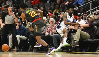 Orlando Magic forward James Ennis III (11) goes into the seats after going for the ball against Atlanta Hawks guard Cam Reddish (22) during the first half of an NBA basketball game Wednesday, Feb. 26, 2020, in Atlanta. (AP Photo/John Amis)