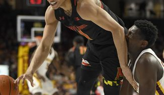 Minnesota's Isaiah Ihnen trips Maryland's Anthony Cowan Jr. (1) as they go for a loose ball during the first half of an NCAA college basketball game Wednesday, Feb. 26, 2020, in Minneapolis. (AP Photo/Hannah Foslien)