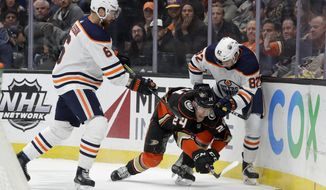 Anaheim Ducks center Carter Rowney goes after the puck between Edmonton Oilers defenseman Adam Larsson, left, and defenseman Caleb Jones during the second period of an NHL hockey game in Anaheim, Calif., Tuesday, Feb. 25, 2020. (AP Photo/Chris Carlson)