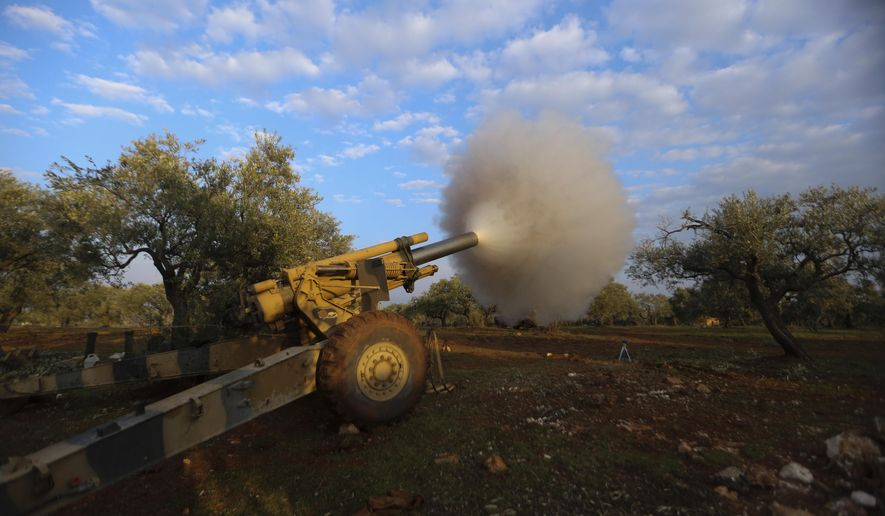 Turkish backed Syrian fighters fire a howitzer near the village of Neirab, in Idlib province, Syria, Monday, Feb. 24, 2020. (AP Photo/Ghaith Alsayed)