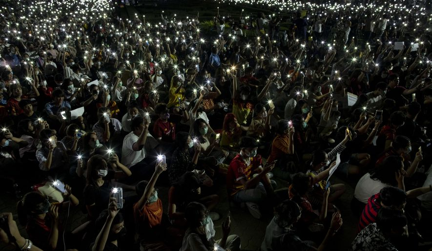 Pro-democracy students wave mobile phones with flashlights switched on, during a large rally at Thammasat University in Pathum Thani, north of Bangkok, Thailand, Wednesday, Feb. 26, 2020. Thailand's normally docile students have been holding large rallies around the country, triggered by a court ruling dissolving a popular opposition political party whose democracy-promoting policies had attracted substantial support among younger Thais. (AP Photo/Gemunu Amarasinghe)