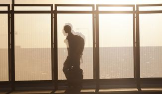 FILE - In this June 26, 2019, file photo a traveller is silhouetted by the setting sun while running past a wind partition in the bus lanes at Denver International Airport in Denver. Whether visiting an exotic destination wedding or just flying back to Cincinnati for your awkward cousin's nuptials, wedding travel can get expensive in a hurry. (AP Photo/David Zalubowski, File)