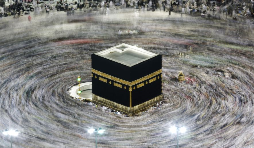 In this Aug. 13, 2019, file photo taken with a slow shutter speed, Muslim pilgrims circumambulate the Kaaba, the cubic building at the Grand Mosque, during the hajj pilgrimage in the Muslim holy city of Mecca, Saudi Arabia. Saudi Arabia on Thursday, Feb. 27, 2020, halted travel to the holiest sites in Islam over fears of the global outbreak of the new coronavirus just months ahead of the annual hajj pilgrimage, a move coming as the Mideast has over 220 confirmed cases of the illness. (AP Photo/Amr Nabil, File)