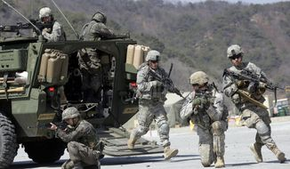 In this March 25, 2015, file photo, U.S. Army soldiers from the 25th Infantry Division's 2nd Stryker Brigade Combat Team and South Korean soldiers take their positions during a demonstration of the combined arms live-fire exercise as part of the annual joint military exercise between South Korea and the United States at the Rodriquez Multi-Purpose Range Complex in Pocheon, north of Seoul, South Korea. The South Korean and U.S. militaries have postponed on Thursday, Feb. 27, 2020, their annual joint drills out of concerns over a virus outbreak. (AP Photo/Lee Jin-man, File)