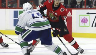Ottawa Senators defenseman Thomas Chabot (72) attempts to move the puck past Vancouver Canucks defenseman Quinn Hughes (43) during second-period NHL hockey game action in Ottawa, Ontario, Thursday, Feb. 27, 2020. (Fred Chartrand/The Canadian Press via AP)