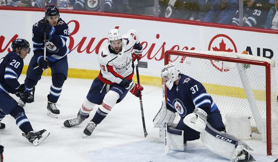 Winnipeg Jets goaltender Connor Hellebuyck (37) stops the wrap-around attempt by Washington Capitals' Tom Wilson (43) during the third period of an NHL hockey game Thursday, Feb. 27. 2020, in Winnipeg, Manitoba. (John Woods/The Canadian Press via AP)