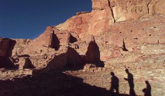 FILE - In this Nov. 21, 1996, file photo, tourists cast their shadows on the ancient Anasazi ruins of Chaco Culture National Historical Park in New Mexico. Lawmakers from the country's largest American Indian reservation may have thrown a wrinkle into efforts aimed at establishing a permanent buffer around the national park as New Mexico's congressional delegation, environmentalists and other tribes try to keep oil and gas development from getting closer to the World Heritage site. Navajo Nation delegates voted Thursday, Jan. 23, 2020, to support a buffer only half the size of the one proposed in legislation pending in Congress. (AP Photo/Eric Draper, File)