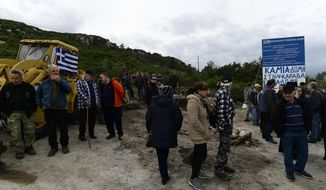 Local residents gather at a roadblock in Karava, on the northeastern Aegean island of Lesbos, Greece, Thursday, Feb. 27, 2020. Greece's government hoped to defuse tensions after protests over plans for new migrant camps on two of its islands Wednesday turned into violent clashes between police and local residents, some armed with Molotov cocktails and shotguns.(AP Photo/Michael Varaklas)