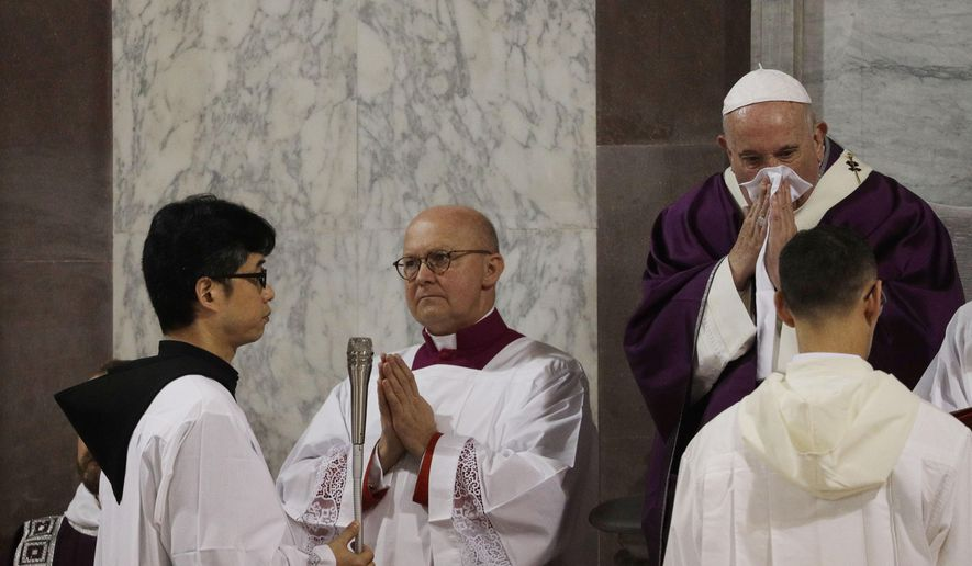 Pope Francis wipes his nose as he celebrates the Ash Wednesday Mass opening Lent, the forty-day period of abstinence and deprivation for Christians before Holy Week and Easter, in the Santa Sabina Basilica, in Rome, Wednesday, Feb. 26, 2020. Pope Francis celebrated the Ash Wednesday ritual kicking off the Catholic Church's Lenten season in traditional fashion, while other Masses in northern Italy were canceled over fears of the new coronavirus.  (AP Photo/Gregorio Borgia)