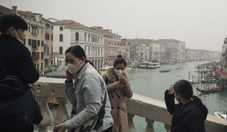 In this Feb. 25, 2020, file photo, tourists fiddle with their protective face masks as they take selfies atop Rialto bridge in Venice, Italy. Still reeling from the effects of major flooding just a few months ago, Venice faces a new emergency: the threat of a new virus outbreak across Italy that is scaring international visitors world-wide and hitting the economy hard. (AP Photo/Renata Brito)