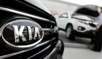 FILE - In this Oct. 23, 2009 file photo, a Kia Motors Corp. employee looks into a Kia vehicle at its showroom in Seoul. Kia is recalling more than 193,000 cars and minvans in yet another move to fix nagging problems that could cause engine fires. The largest of two U.S. recalls released by the government Thursday, Feb. 27, 2020, covers certain 2013 and 2014 Optima midsize cars.   (AP Photo/ Lee Jin-man, File)
