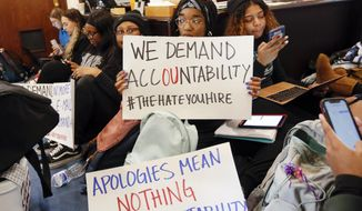 Oklahoma University students participate in a sit-in organized by the Black Emergency Response Team student group outside of the office of OU provost Kyle Harper in Evans Hall at the University of Oklahoma in Norman, Okla., Wednesday, Feb. 26, 2020. The protest comes after two incidents where faculty members used a racial slur while teaching. (Nate Billings/The Oklahoman via AP)