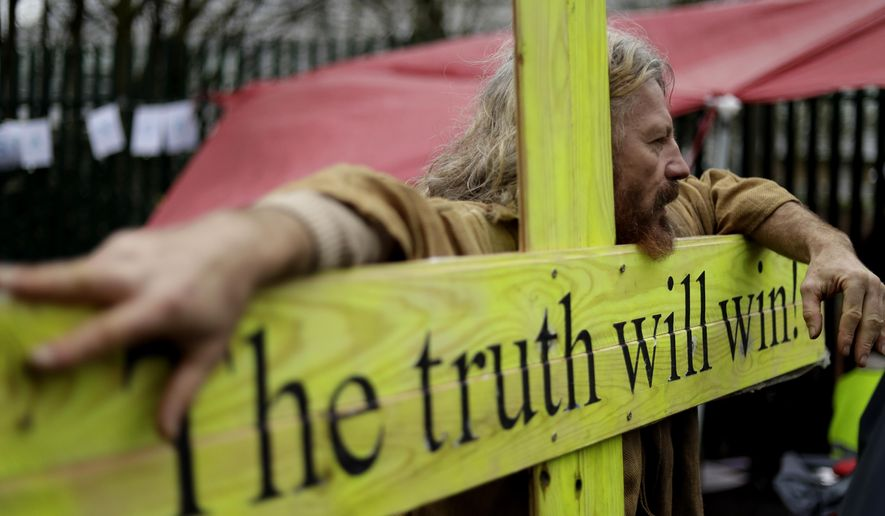 """A supporter leans on a wooden cross which reads """"The truth will win"""" as he protests against the extradition of Wikileaks founder Julian Assange outside Belmarsh Magistrates Court in London, Monday, Feb. 24, 2020. The U.S. government and Assange will face off Monday over extradition, a decade after WikiLeaks infuriated American officials by publishing a trove of classified government documents. (AP Photo/Matt Dunham)"""